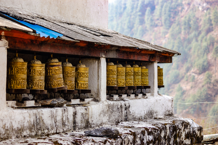 The brass prayer wheels  lined up under the wooden roof in a village on the Everest base camp trekking route in Himalayas on a foggy day.