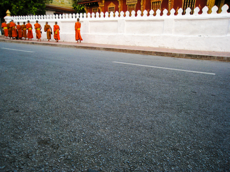 alms: Monks walk in the line on footpath beside the white temple fence back to Wat Saensoukaram in Luang Prabang from begging alms in early morning.