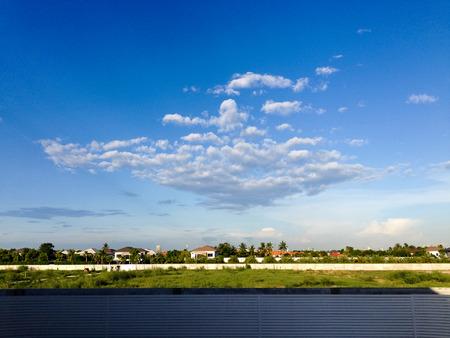 samutprakarn: Horizontal view of houses in a village of suburban Bangkok, Samutprakarn province,  with white cloud and blue sky. Stock Photo