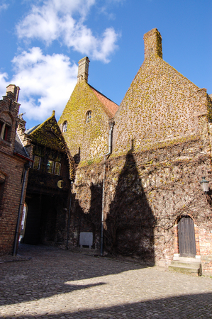 house gable: The shadow of a gable house on the brick wall partly covered with ivy and a wooden door beside, on a cobblestone street in Bruges, Belgium on white cloud and blue sky day.