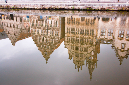 still water: The reflection of the old historic buildings in still water along the waterfront of Leie river in Ghent, Belgium.