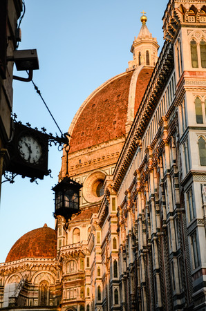Duomo of Florence, Santa Maria del Fiore, with foreground of a clock and hanging lamp in the evening.