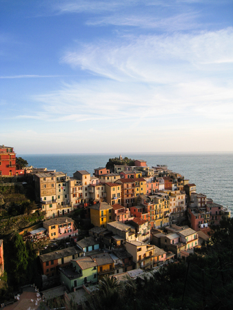 spezia: Many old colorful traditional Italian houses on hillside in Manarola, a fisherman village of Cinque Terre in the province of La Spezia, Liguria, Italy with Ligurian sea background in white cloud and blue sky on sunshine evening. Stock Photo
