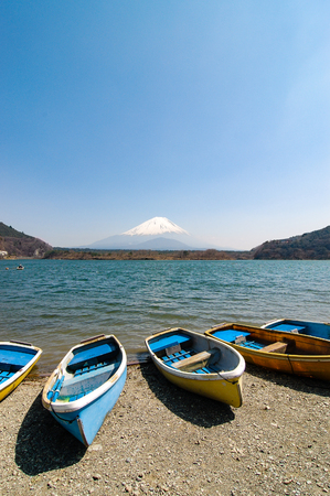 The fishing boats on the shoreline of Shoji Lake in Yamanashi Prefecture of Japan with Mount Fuji (Fujisan) behind in bright blue sky on sunshine.