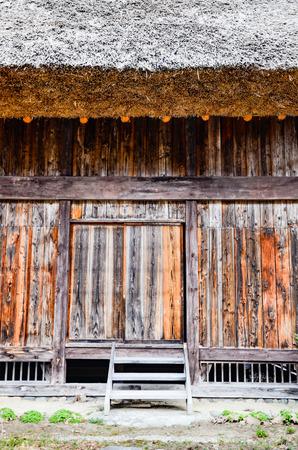 Thatched steep roof detail and wooden wall and door of traditional gassho zukuri house at historic Shirakawa-go village in Gifu, Japan
