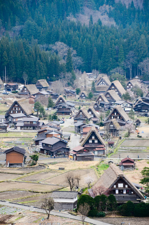gassho zukuri: Aerial view of historical village, Shirakawa-go in Gifu Prefecture, the traditional Gassho-zukuri houses as UNESCO World Heritage Site, with the green forest in background.