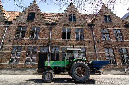 Bruges, Belgium - April 15, 2011: A green bulldozer was driven on an old cobblestone street passing the traditional Belgian brick houses in quiet residential area of Bruges on a sunny day.