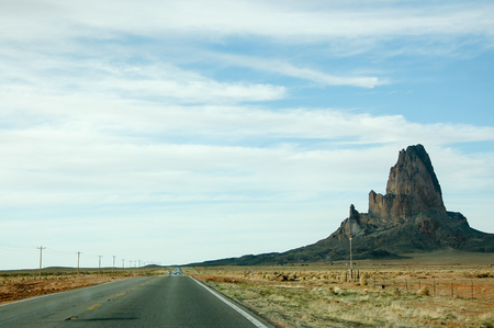 county side: Outstanding Agathla Peak from surrounding terrain on the sideways with electric pole along the highway of the U.S. route 163 from south to north with white cloud and blue sky on sunshine day, this road leading to Monument Valley in Arizona. Editorial