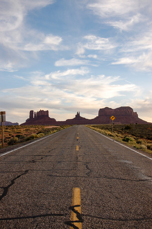 monument valley view: The scenic highway of U.S. Route 163 in Utah leading south to Arizona, through the red rocks of Monument Valley, with traffic sign on foreground in white cloud and blue sky on evening sunshine in vertical view.