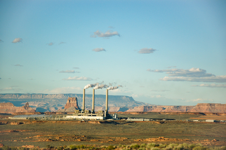 generating station: Three smokestacks of Navajo Generating Station in Page, Arizona, a coal-fired power plant, with mountain backdrop in bright blue sky and little white cloud on evening sunshine.