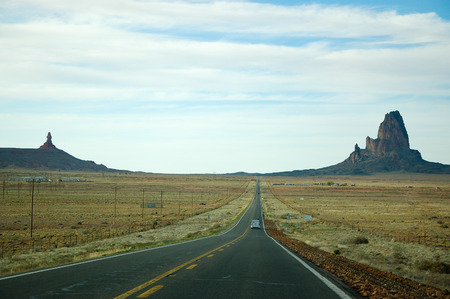 county side: Outstanding Agathla Peak from surrounding terrain on the sideways with electric pole along the highway of the U.S. route 163 from south to north with white cloud and blue sky on sunshine day, this road leading to Monument Valley in Arizona. Stock Photo
