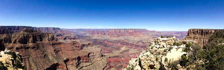 Skyline scenery in panorama view on the South Rim Trail at Grand Canyon National Park, Arizona in horizontal view with bright blue sky on sunshine day. Stock Photo