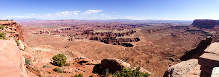 Scenery of Grand view point overlook in panorama at Island in the Sky, Canyonlands near Moab in Utah, with bright blue sky and white cloud on sunshine day.
