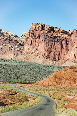 scenic drive: The red rock formation scenery with the curved road of the scenic drive at Capitol Reef National Park in Utah with bright blue sky on sunshine day in vertical view. Stock Photo