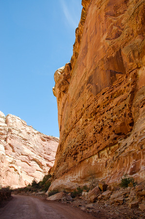 scenic drive: The red rock cliff besides the rough road through Capitol Gorge of Capitol Reef National Park in Utah with bright blue sky on sunshine day in vertical view. Stock Photo
