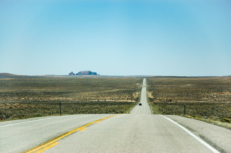 faraway: The long and straight highway among the plain in desert area of Utah with a rock mountain faraway backdrop in bright blue sky on sunshine day in horizontal view.