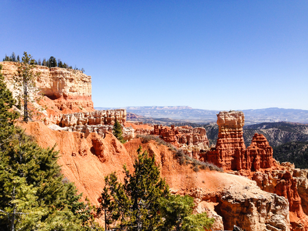 hunters tower: Scenery of The Hunter, outstanding hoodoos in red rock formations, with mountain backdrop at Agua Canyon overlook of Bryce Canyon National Park, Utah in bright blue sky on sunshine in horizontal view.