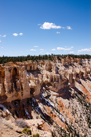 Scenery of grottos in red rock formations with green forest backdrop at Bryce Point overlook of Bryce Canyon National Park, Utah in bright blue sky and white cloud with sunshine in vertical view.