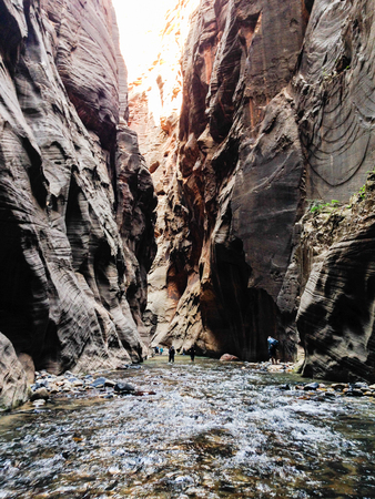 View of the Virgin river and the natural high rock wall from hiking in The Narrows upstream from the Temple of Sinawava, one of the most popular hikes in Zion National Park.