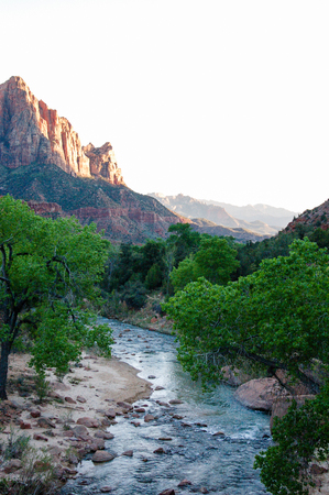 a watchman: Scenery of The Watchman and the Virgin river with green trees alongside and bright sky in evening sunshine, view from the bridge on Zion-Mount Carmel highway at Zion National Park, Utah.
