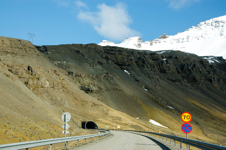 A tunnel with the speed limit sign on the Ring Road of Iceland or Route 1 (a popular road trip for tourists and mostly paved with asphalt) in a blue sky on sunshine day with snow mountain backdrop around the eastern Iceland. Stock Photo