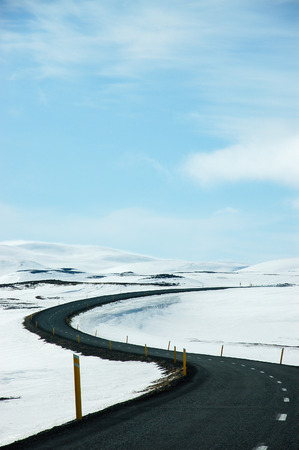 Scenery of the long and winding road to the Dettifoss, a famous waterfall in northeast Iceland. The black asphaltic road with yellow street colonnade pillars contrast the snow alongside with blue sky.