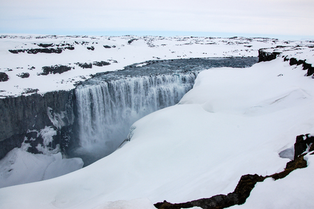 Dettifoss, the most powerful waterfall in europe and on a popular tourist route (the Diamond Circle) in North Iceland, with fully snow around on a cloudy day at the viewpoint on the west bank. Stock Photo
