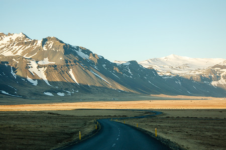 Scenery of a winding road through the brown pasture with snow-capped mountain background at Snaefellsnes peninsula in west coast of Iceland during road trip with blue sky on evening sunshine .