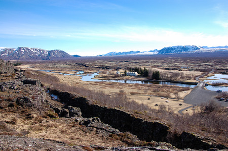 Thingvellir national park, famous tourist destination of the golden circle tour in southwestern Iceland, scenery of the faraway small chapel and oldest parliament with foreground of the crack and river, snowcapped mountain backdrop on sunny day with blue  Stock Photo