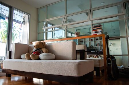 Teddy bear sitting on the sofa with cushions in the decorated living room of the middle-class condominium located in the heart of Bangkok.