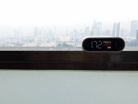 Air pollution detector shows the result from PM2.5 dust (Fine Particulate Matter) with background of smog cityscape of Bangkok , Thailand in the morning.