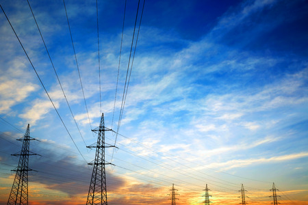 high voltage: Pylons and power lines at sunset with vibrant sky,clouds and sun
