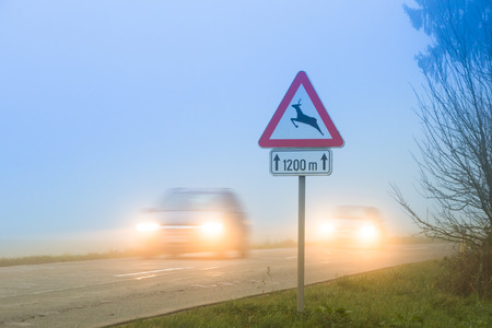 road conditions: Cars passing a traffic sign for deer crossing in fog Stock Photo