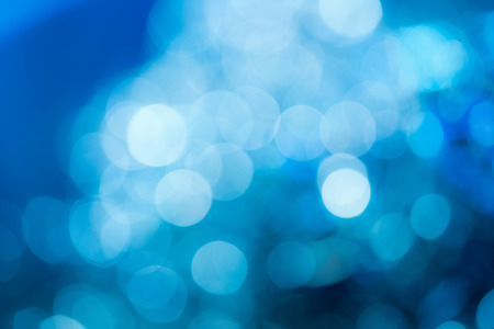Blue holiday party background. Abstract with bright twinkles, sparkles, blurred, defocused light.