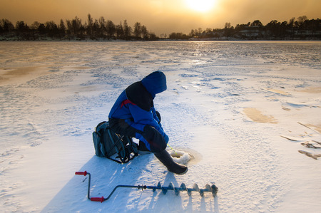 auger: Ice fishing on thick ice with hand ice auger in front