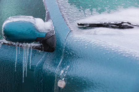 Frozen rearview mirror and wiper of the car with icicles, ice and frost photo