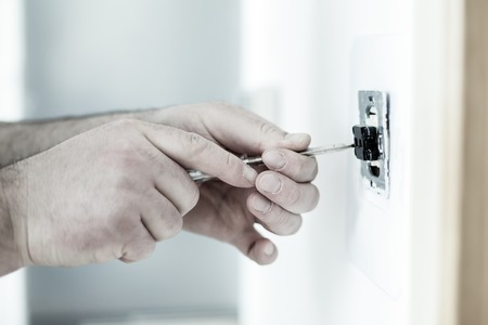 energy electrician: Man installing light switch with screwdriver after home renovation
