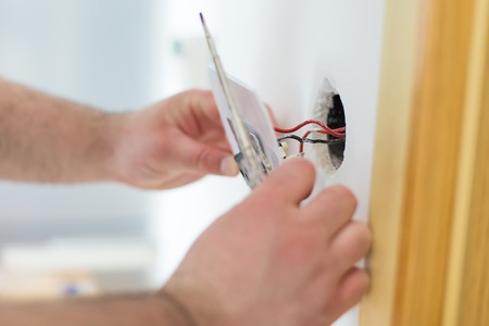 Man installing light switch after home renovation