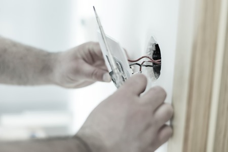 energy electrician: Man installing light switch after home renovation