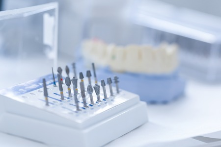 prosthodontics: Variety of tools: ceramic preparation kit with dental mold in the background