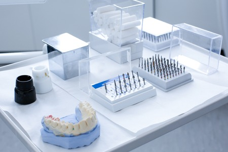 Variety of tools in dentists office: ceramic preparation kit and various dental burs with dental mold on a tray photo