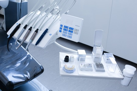 Dentists office - specialist tools, drills, handpieces and laser with polish nozzles, drill nozzles and denture model on the tray photo