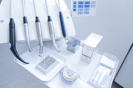 professional practice: Dental practice - specialist tools, drills, handpieces and laser with polish nozzles, drill nozzles and denture model in the foreground