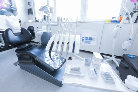 Dentists office with chair, tools and drills in the foreground