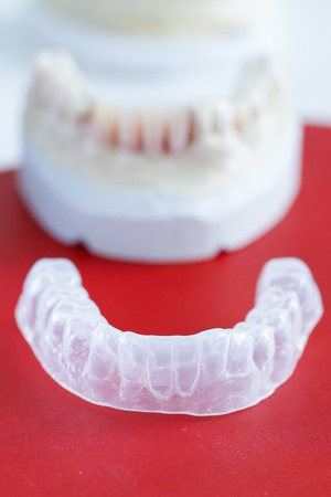 Invisalign, invisible plastic teeth aligner with dental plaster mold in the background