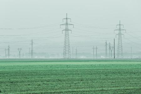 torres el�ctricas: Torres de alta tensi�n para una tensi�n diferente en un campo verde Foto de archivo