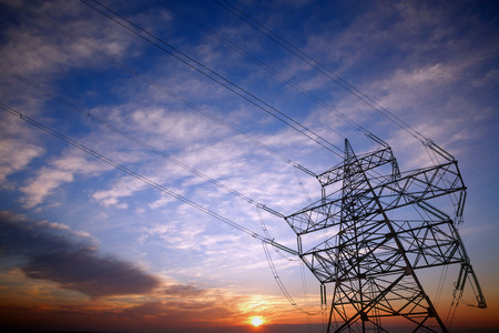 electricity supply: Pylon and power lines at sunset with nice sky and sun Stock Photo