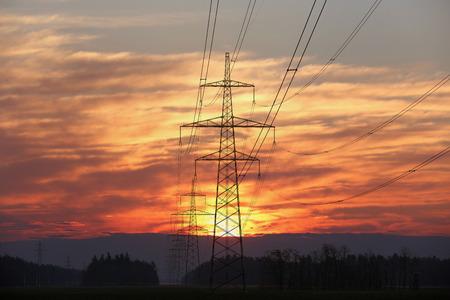 Pylon i linie energetyczne o zachodzie słońca z czerwonym niebem i słońcem