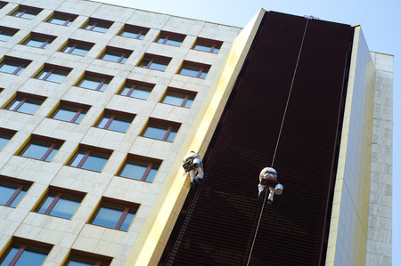heights job: Two men working high on a facade Stock Photo