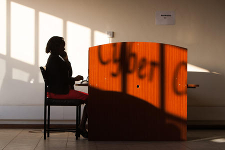 Silhouette of african woman making phone call in internet cafe photo